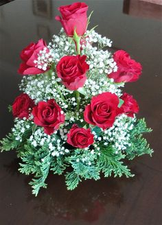 A small display of roses with baby breathe and fir