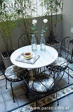 El patio es el correlato perfecto de la cálida decoración planteada en todo el departamento. Allí, sobre el piso de calcáreos con guardas hecho a nuevo (Entorno) se acomoda el juego de jardín con sillas de hierro y mesa con tapa de mármol de Carrara ( $ 399,90 c/u y $ 549, Morph). Los almohadones con estampado toile de jouy ($ 79 el metro de 1,40 de ancho, De Levie) resultan el complemento justo para esta propuesta. Sobre la mesa, un cuaderno forrado en tela ...