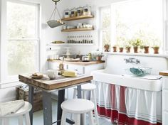 Here, white paint and rope pulls transformed off-the-rack cabinets, while humble butcher-block counters take the place of pricey marble or granite. DIY accents, like a tablecloth-turned-sink skirt, deliver one-of-a-kind style for a song. Glass jars keep pantry staples on open shelving. Everything makes for a cheap and chic rustic country kitchen!