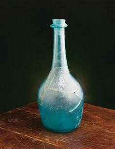 Cette bouteille à boisson alcoolisée, de type pot-de-fleurs en verre commun bleu-vert, était-elle destinée au service à table ou s'agit-il d'une simple variante de ce modèle ? Assez rare, elle tient de la bouteille par sa forme et du flacon par son matériau. Elle a été découverte sur le site de la maison Le Picart, dans un contexte archéologique du XVIIIe siècle. Photo : Marc-André Grenier 1998 © Ministère de la Culture et des Communications