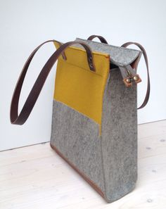 Frontview of the felt shopper xl with the yellow panel. The back is plain grey. Here you can also see the leather that protects the bottom of the bag. You can buy it in my Etsy shop: https://www.etsy.com/nl/listing/212040334/grote-shopper-tas-van-vilt-en-leer-in