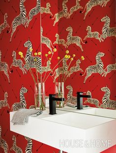 This playful main-floor powder room offers guests a burst of color —and a movie reference to boot. The zebra-printed wallpaper is straight out of Margot Tenenbaum's bedroom inThe Royal Tenenbaums. Photographer: Stacey Brandford | Designer: Shirley Meisels