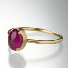 An 18K yellow gold ring with a 1.4mm, full round band and an oval ruby measuring 8.7mm x 7.1mm. Size 7.5.