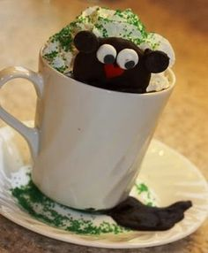 Groundhog Hot Cocoa!!  TOO CUTE! Just add edible eyes and a heart sprinkle for a nose, choco chips for ears. Then melt a little chocolate and put on the inside edge of mug, stick cookie to it and chill in refrigerator. Put a chocolate shadow on the saucer and in the morning serve hot cocoa to the kids as they watch Phil get shoved out of his tree trunk! :-) jh