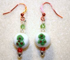 Handcrafted by Teal Palmetto, LLC. You get lots of sparkle in these Christmas tree earrings!  The glass Christmas tree focal beads are complemented by red, green, and clear glass seed beads.  Each earring also has a tiny clear Swarovski crystal bead at the bottom.  These earrings have red fish hook ear wires. Price: $15.