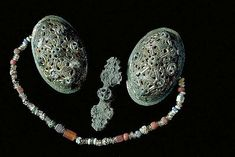 Beads. Glass.  Viking. The glass beads hung between two tortoise brooches. Grave find, Björkö, Adelsö, Uppland, Sweden.  SHM 34000:Bj 1081