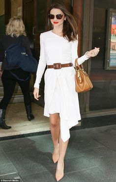 Miranda Kerr looking chic in a simple white dress paired with tan accessories and red lipstick.
