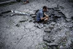 ウクライナ東部ドネツク(Donetsk)で、砲撃により地面に開いた穴を撮影する男性(2014年7月29日撮影)。(c)AFP/BULENT KILIC ▼30Jul2014AFP|欧米、対ロシア制裁強化を決定 金融・防衛部門など対象 http://www.afpbb.com/articles/-/3021795