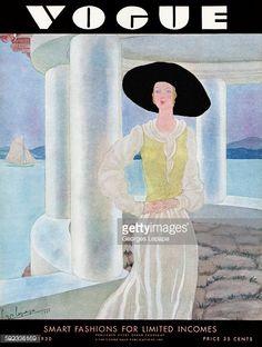 Woman in black hat standing on veranda with ocean view in background