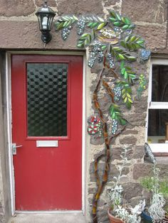 The planning of this mosaic was done during the May 2009 Mosaic Your Garden course, as were the various sections (groups of leaves, Wisteria flowers & birds/bugs).  Due to poor weather conditions, it only recently got put into place.  It incorporates beer & wine bottle glass, ceramics & glass beads