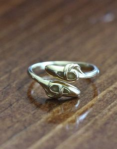 This gold ballet shoes ring is a perfect gift for your smiling dancer at her next dance recital or birthday! The ring features an adjustable band accented with ballet slippers and can expand as your special ballerina dancer grows. Sterling silver. Gold Plated. One size fits all.