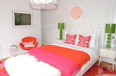 Fun teen girl's bedroom features a West Elm Window Bed dressed in pink and orange bedding flanked by Mid-century Nightstands topped with green pagoda lamps by Worlds Away alongside a red Arne Jacobsen Swan Chair next to a lucite accent table atop a red and orange floral rug.