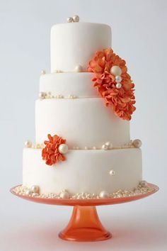 Understated Elegance Wedding Cake. Pearls add a glam touch to a simple cake. Punch it up with brightly-colored flowers.