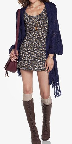 Boho chic fall/winter look with baggy sweater, patterned dress, long socks, and tall boots