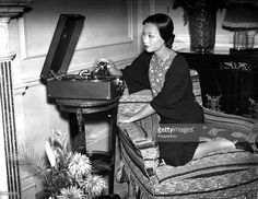 November 1934, American actress Anna May Wong pictured at her home playing a record on her gramophone player Credit: Popperfoto