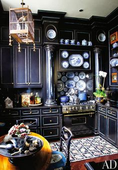 What a kitchen -- black cabinets and a hanging bird cage. Wonderful, from Architectural Digest