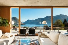 Breathtaking lake view seen through the giant sliding glass panel in this living room. White sofas face each other over an all-glass coffee table, with metal framed, black leather chairs seated in front.