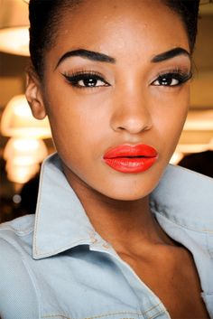Orange lips with a cat eyeliner and lush lashes