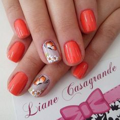 Paint your nails in bright orange and cream color combination. The design features a plain orange and cream base color. Small white flowers and orange butterfly details are added on top.