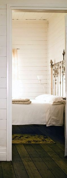 I would love to have an old, metal headboard. The lighting in this room is nice as well. White walls and sheets. Light and airy.