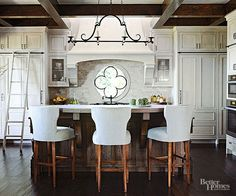 If your taste runs a bit sleeker than conventional Tuscan style, take inspiration from this modern kitchen that pares down the best of Tuscany. The cabinets have raised panels and the island boasts beefy corbels, but they're far more streamlined than most. The chandelier, with its elegant wrought-iron curves, is a simpler take on an ornate overhead fixture. And limiting the color palette to high-contrast creamy white and deep-hue wood is playful but still sophisticated./