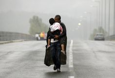 Syrian refugee kissing his daughter as he makes his way towards the Macedonian…
