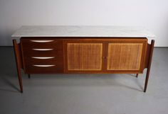 About this STUNNING Mid Century Modern Teak Credenza/Buffet Are you seeing this? Absolutely gorgeous grain layout on this versatile piece. A stance unlike any other with an astounding marble top. Be it In your family room, bedroom, entry way, or office, this piece will create a powerful pop to your current aesthetic. This has been so amazingly well kept as it comes in at an easy 8 out 10 and needs nothing. Stunning. Make it yours today!   Dimensions  Wide- 68 Depth- 19 Height- 35    Ship...