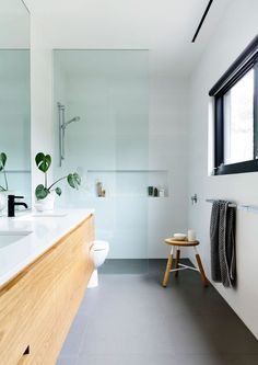 Dark grey tiles on floor, light white walls, timber vanity with black tap ware. Awesome bathroom!