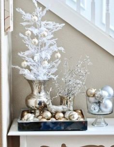 gold ornaments on display and on a snowy Christmas tree