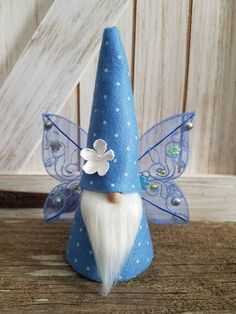 This mini fairy gnome is in periwinkle and white polka dots. He has matchimg fairy wings He has a white soft beard and the hat has a white flower on it. He stands 5 inches high