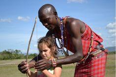 Maasai guide teaching a your girl archery at Encounter Mara safari camp