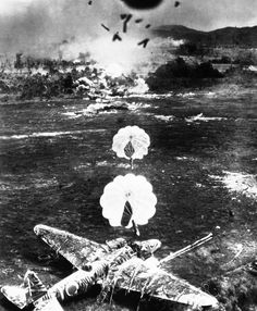 "Para-frag bombs fall toward a camouflaged Japanese Mitsubishi Ki-21, ""Sally"", during an attack by the US Army Fifth Air Force against Old Namlea airport on Buru Island, Dutch East Indies, on October 15, 1944. A few seconds after this picture was taken the aircraft was engulfed in flames. The design of the para-frag bomb enabled low flying bombing attacks to be carried out with higher accuracy."