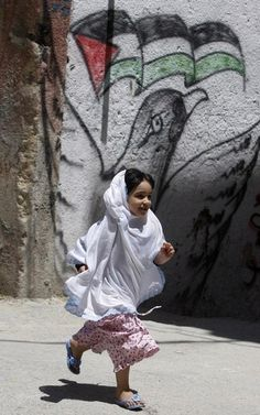 A girl runs past a Palestinian flag spray painted on a wall in the Balata refugee camp, near the West Bank city of Nablus May 11, 2011.