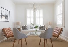 A slip-covered white sofa from Julie Neill Designs anchors a deft mix  of furnishings. Pillows from Shaun Smith Home; art by David Spiellman; Barcelona chairs, from the owner's collection