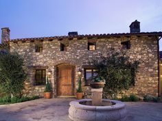rustic stone exterior with brick-lined doorway, fountain, round driveway, and wood windowsills