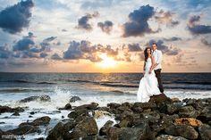 Bride & groom on coastal beach rocks during sunrise at thier Jekyll Island destination wedding.    http://www.matthewdruin.com/blog/weddings-2/sadie-ryan-jekyll-island-destination-wedding/