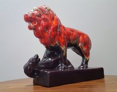 Striking pottery Lion over its prey, deer or gazelle. The lion is done in a red, orange and yellow drip glaze. The bottom of the lion, deer and base are done in brown. The stamp on the bottom is CAC Canada and what appears to be the mold number, I cannot make out. It is in good condition with no chips or cracks. This piece will certainly dominate its space.