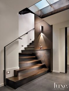 Love these stairs, panelled wall, and sleek light fixture