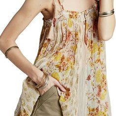 """(Free People) Romantic & Feminine top. New w tags. Tassel-trimmed spaghetti straps suspend the swingy silhouette of a floral-print tank done in groovy '70s hues. A keyhole at the smocked neckline offers a flirty flash of skin, white side slits add extra movement to the billowy look. 25"""" length (size Medium).Front keyhole with rouleau-button closure.Square neck.Adjustable spaghetti straps with tie closure.Semi-sheer; base layer recommended.100% viscose.Dry clean or machine wash cold, tumble…"""