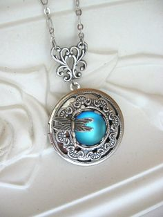 Midday  This beautiful locket features a luminous, crystal cabochon that shimmers from blue to green resembling a pond or lagoon in the midday sun.