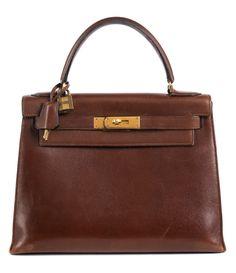 Ca. 22 x 28 x 10 cm. Lederhandtasche in Braun mit goldfarbenen Beschlägen. Innenraum mit einem Reißverschluss- und zwei Steckfächern. Anbei Originalschloss...