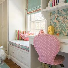 Gorgeous girl's bedroom with mirrored closet and built-in desk with shelving situated next to a storage window seat accented with a Thomas Paul Aviary Robin ...