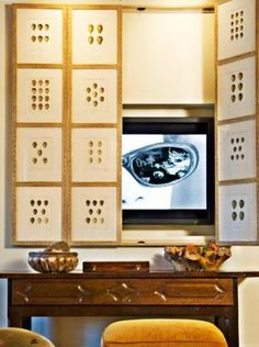 Hiding TVs behind hinged and sliding doors or wall decorative panels. I like subtle Asian flare mah Jong tiles inspired