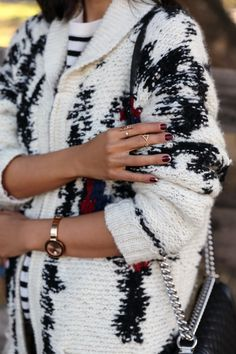 cozy sweater, gold rings, red nails
