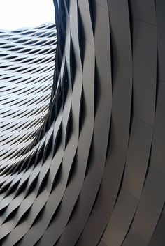 modernization of messe basel, switzerland by herzog & de meuron. brilliant exterior facade of metallic waves.