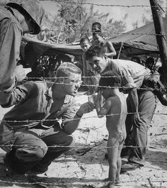 Marines try to soothe a crying toddler with a rations tin at a refugee camp on Saipan.
