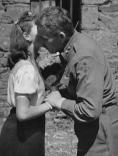 """A member of the U.S. 4th Infantry Division gets a """"French kiss"""" from an appreciative girl somewhere on the road to Paris, 1944. This photograph captures the essence of the liberation: the gratefulness of the liberated and the humility of the liberator. Photo from the Webmaster's collection."""