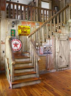 Julie sought out as much reclaimed red barnwood as she could get, resulting in washes of the nostalgic color throughout the house. The railing, like that on the front porch, is made of poles salvaged from Virginia tobacco barns. Retro metal signs add a graphic touch to the stairway.