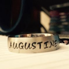 "Sterling silver ring reading ""Augustine."""