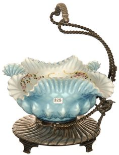 "14 1/2"" X 10"" BRIDES BASKET: BLUE SATIN DIAMOND QUILTED MOTHER-OF-PEARL, MELON RIBBED, SQUARE RUFFLES, ART GLASS BOWL WITH WHITE INTERIOR AND ENAMELED FLORAL HIGHLIGHTS - SET ON MERIDEN SILVERPLATE STAND WITH SPIRAL TWIST ARM AND FIGURAL BIRD DESIGN"